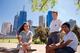 three students sitting in the park on a sunny day